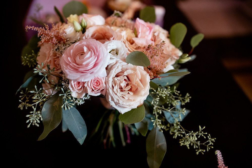 Bride's bouquet of pink and cream colored roses and Persian buttercups.