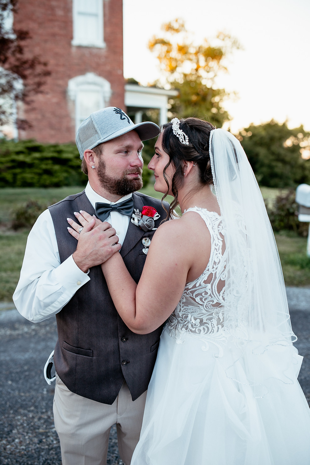 Groom and bride look at each other in front of mansion at The Market at Ebbert Farms in Belmont, OH.