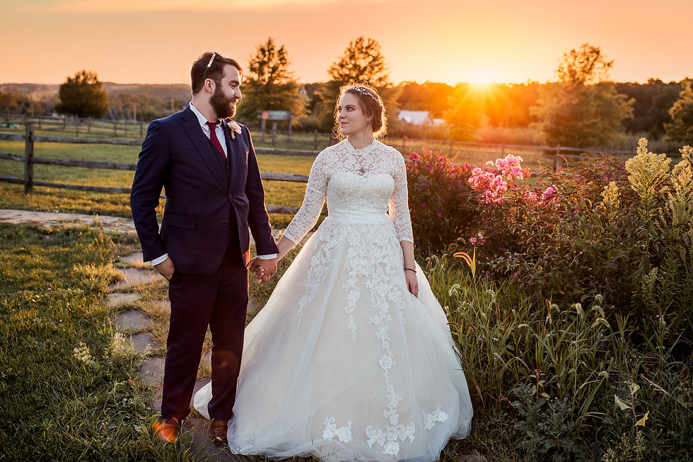 Bride and groom walking and holding hands in front of sunset at Rich Farms in Smithfield, PA