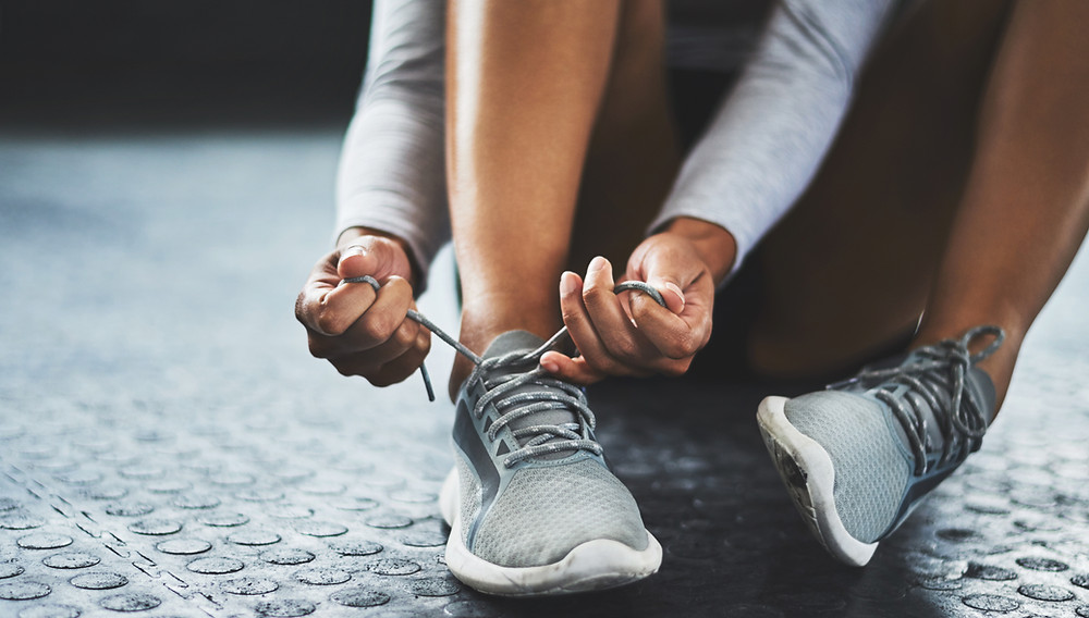 Woman tying up running shoes making her own workout plan