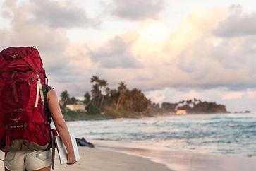 Backpacker mit Laptop am Strand