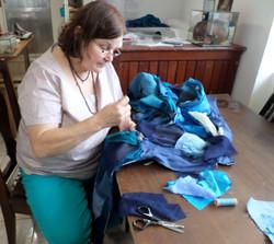Leda costurando a roupa azul