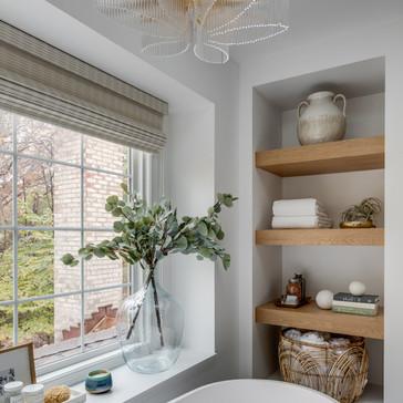 Open shelving in a modern spa-like master bathroom retreat designed by Erika Jayne Design, a Maryland based interior design firm serving the Washington, DC area.