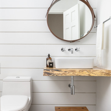 Modern farmhouse powder room with a round mirror, live-edge floating wood vanity, a modern vessel sink, wall mounted faucet, and shiplapped walls designed by Erika Jayne Design, a Maryland based interior design firm serving the Washington, DC area.