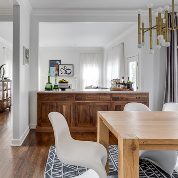 A modern chic dining room with white Panton chairs, wood and gold accents designed by Erika Jayne Design, a Maryland based interior design firm serving the Washington, DC area.