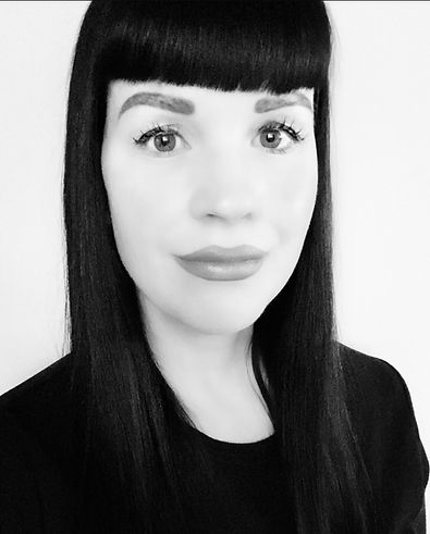 A black and white picture of Stephanie. Stephanie is white, has brown eyes, and long dark hair with short blunt bangs. She is dressed in a black shirt which contrasts against a white background.