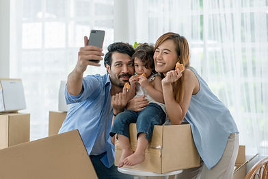 Two adults and a smill child posing for a selfie on top of moving boxes.