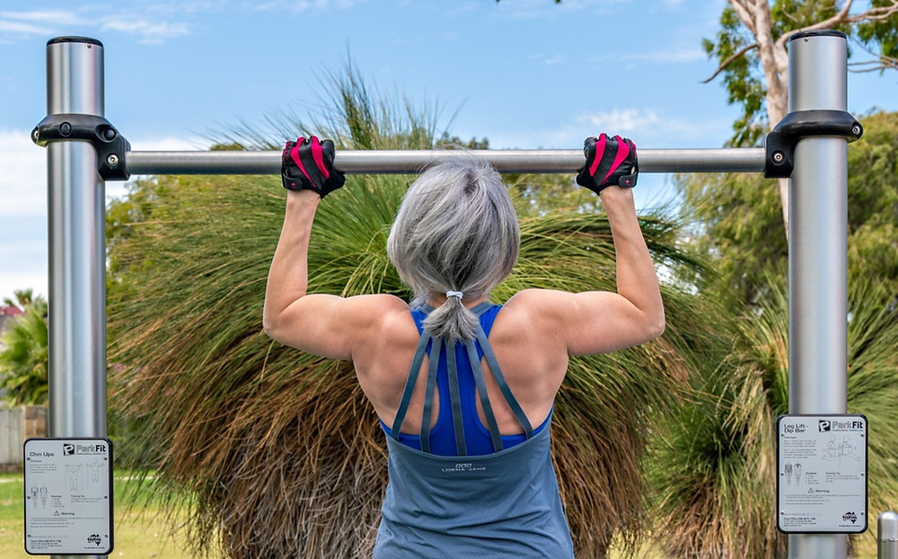 Julia performs a pull up exercise at home in the local park.