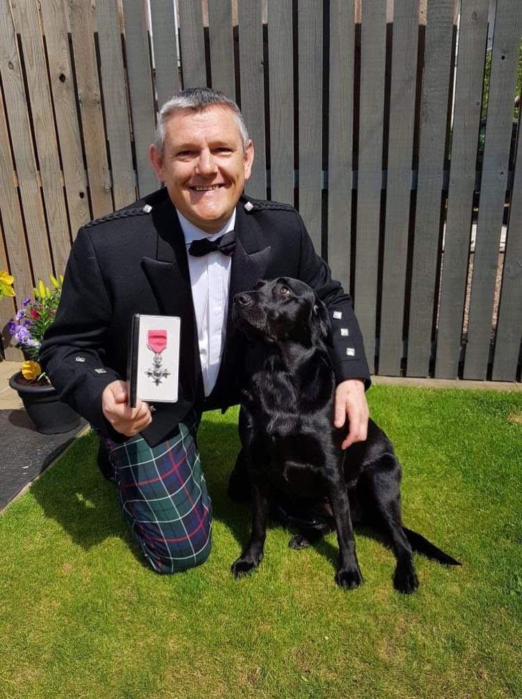Photo of John Davidson holding his MBE medal and his black labrador Suki