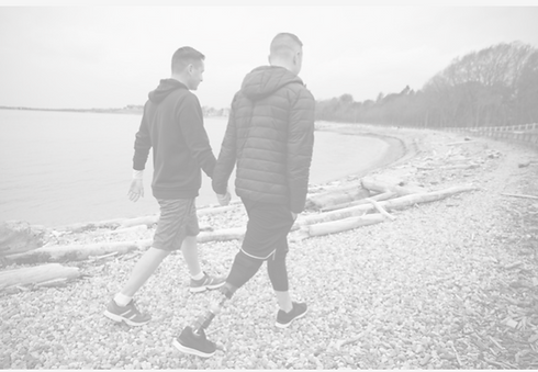 Two white men are holding hands and walking on a beach. The man on the right has a prosthetic leg.