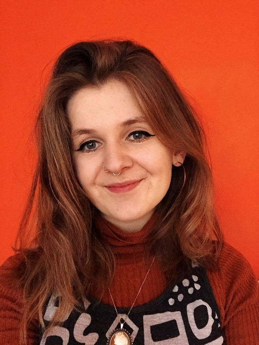 a orange background with a white woman with long hair is swiming. She has an orange turtleneck jumper under black dungerarees which have some white shapes. She is wearing a necklace and smiling at the camera.