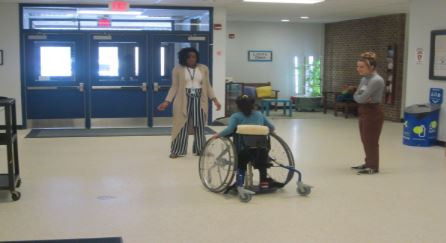 Student in stander receiving instruction