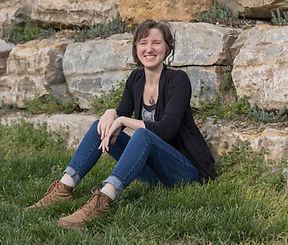 Teri Grunthaner, Expressive Therapist, sittng on the grass with a smile