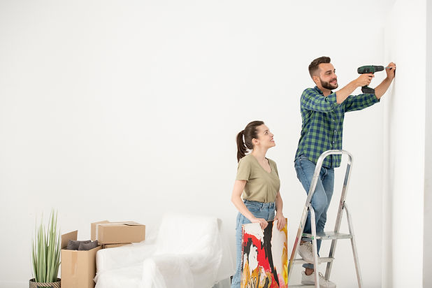 positive-young-man-standing-on-step-ladder-and-using-electric-screwdriver-while-inserting-