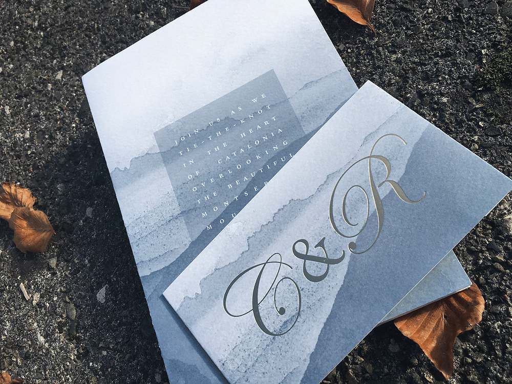 Gold foil letterpress invitation and bellyband with watercolour background