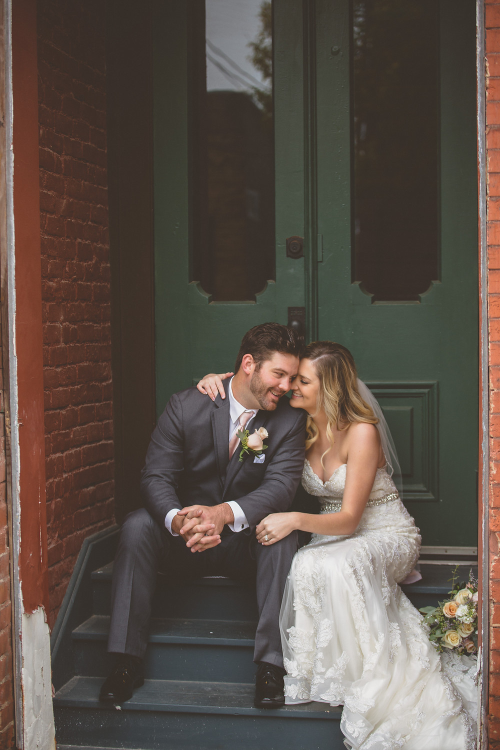 Bride and groom snuggle infront of green doors in downtown Des Moines.