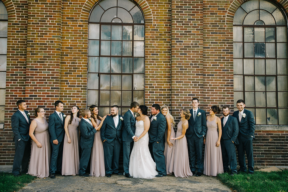 Wedding party in front of a brick wall.