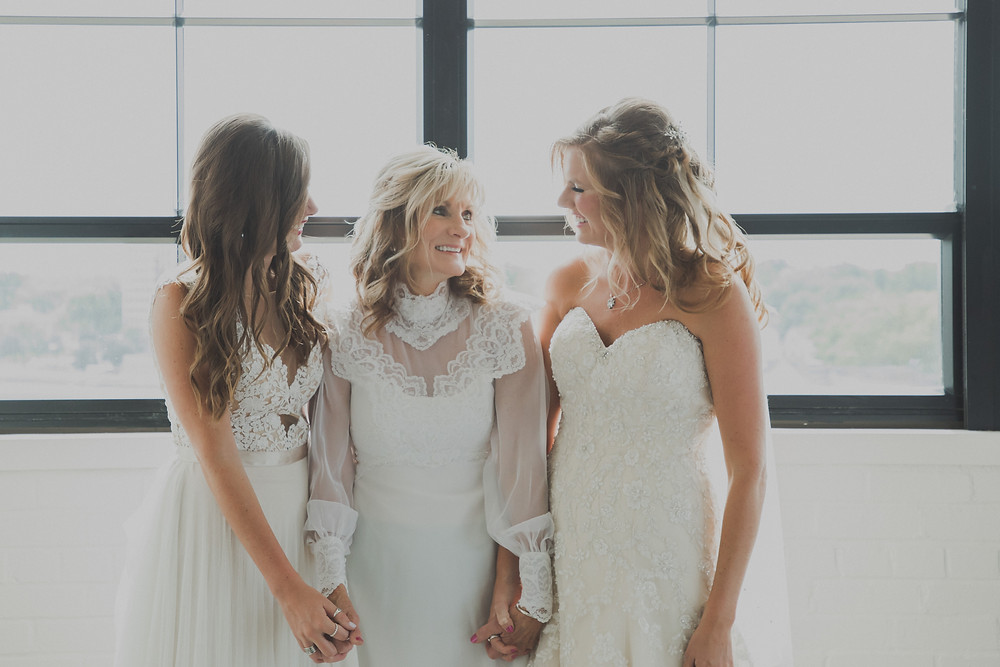 Beautiful mom and her daughters in their wedding dresses.
