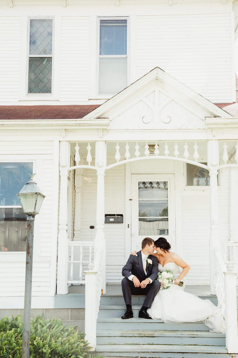Beautiful bride and groom on a white porch.
