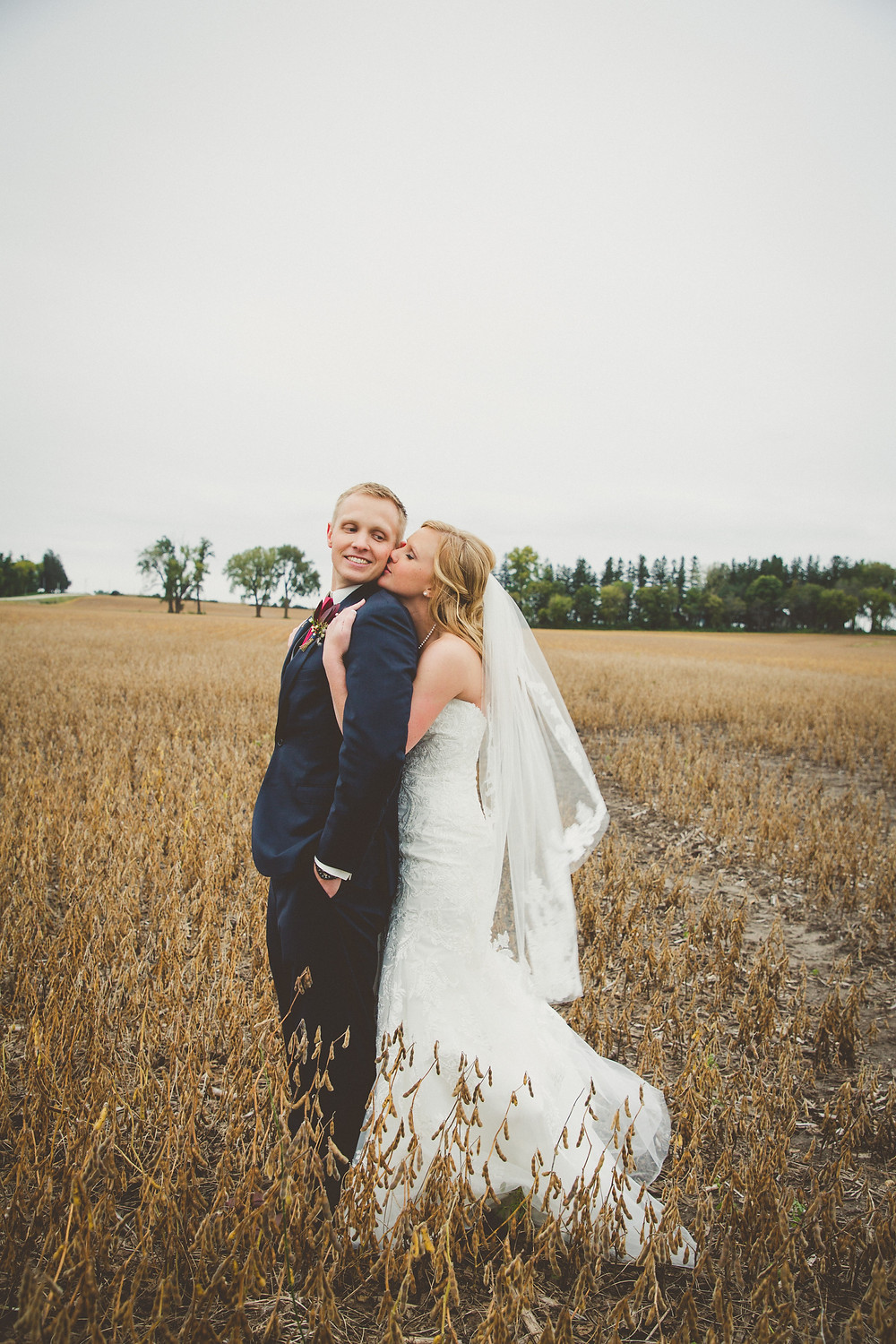 Beautiful bride and groom in a field on their wedding day.