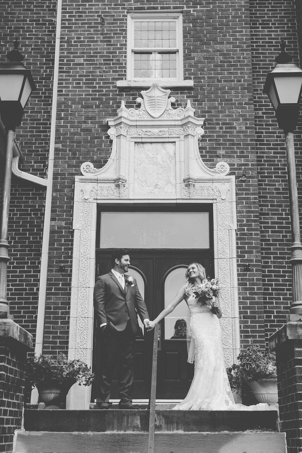Bride and Groom hold hands in Downtwon Des Moines in front of a brick wall.