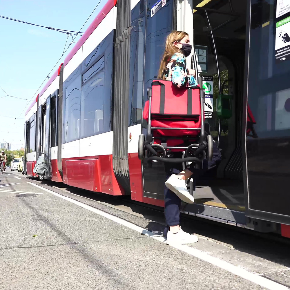 Woman boarding streetcar with cart