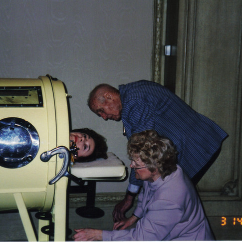Pam Cazzolli inside iron lung invented by Dr Jack Emerson (standing) & Dr Augusta Alba present