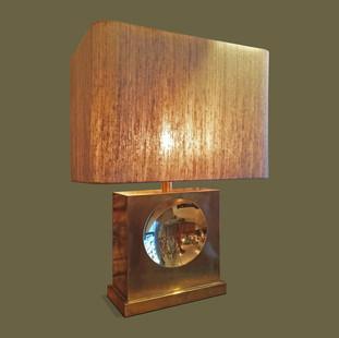 Lámpara de mesa en cobre con gran circulo cóncavo.