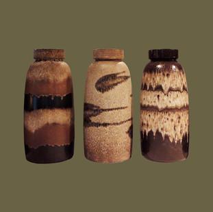 Tres jarrones de arenisca pintados con distintas decoraciones abstractas.