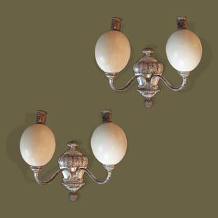 Pareja de apliques de dos brazos en bronce plateado y huevos de avestruz.
