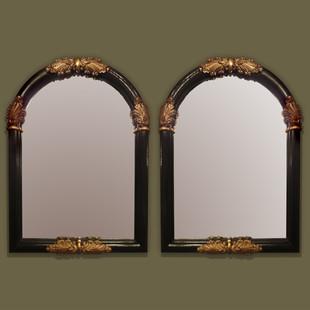 Pareja de espejos en madera ebonizada y tallas decorativas en oro viejo.
