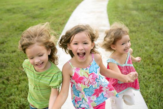 子供達が手をつないで元気いっぱいに笑顔で駆け寄って来るイメージ