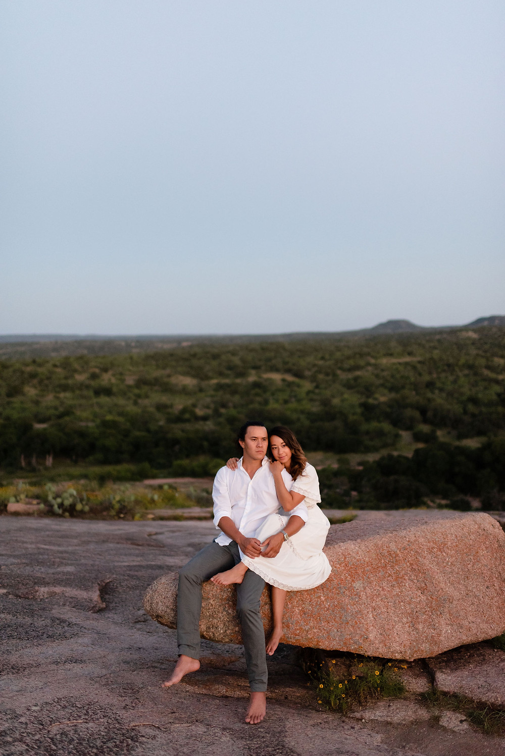 bride sits on groom's lap on a large rock. they watch the sunset together