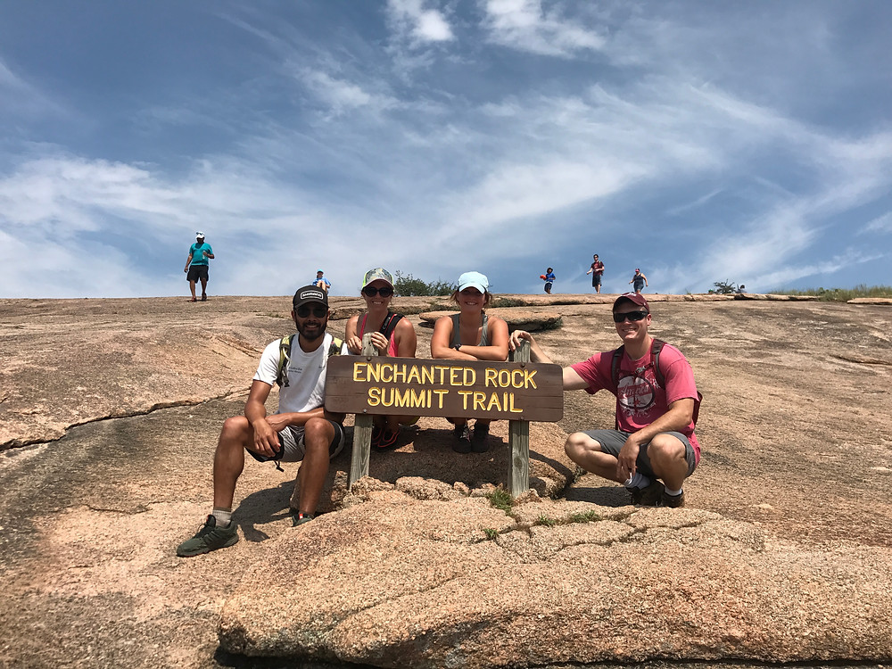 group of hikers at enchanted rock with the enchanted rock summit trail sign