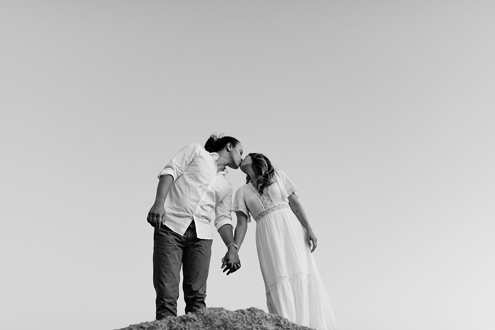 couple standing next to each other holding hands, kissing. the point of view of the camera is from below so you can only see the couple and the sky