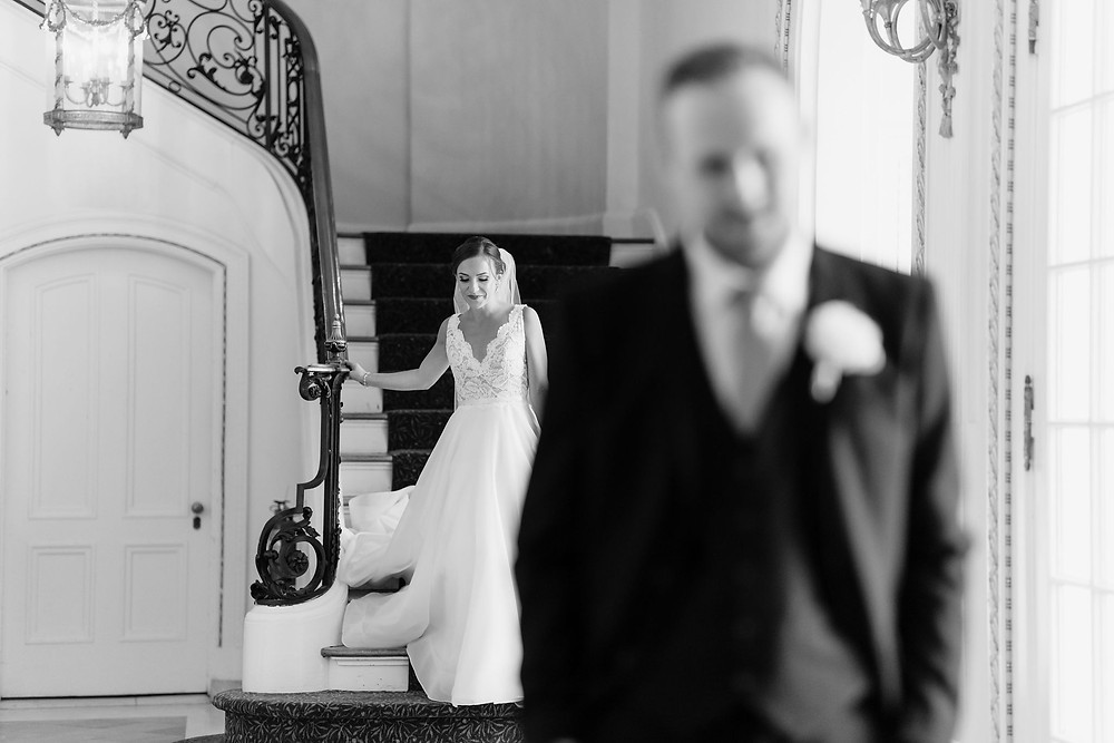 bride walking down grand staircase in the foyer of Tupper Manor for her first look with groom