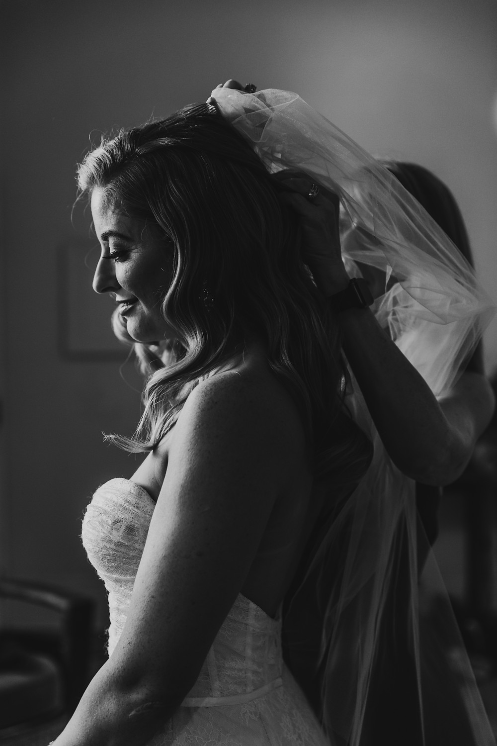 black and white photo of mom putting on bride's veil
