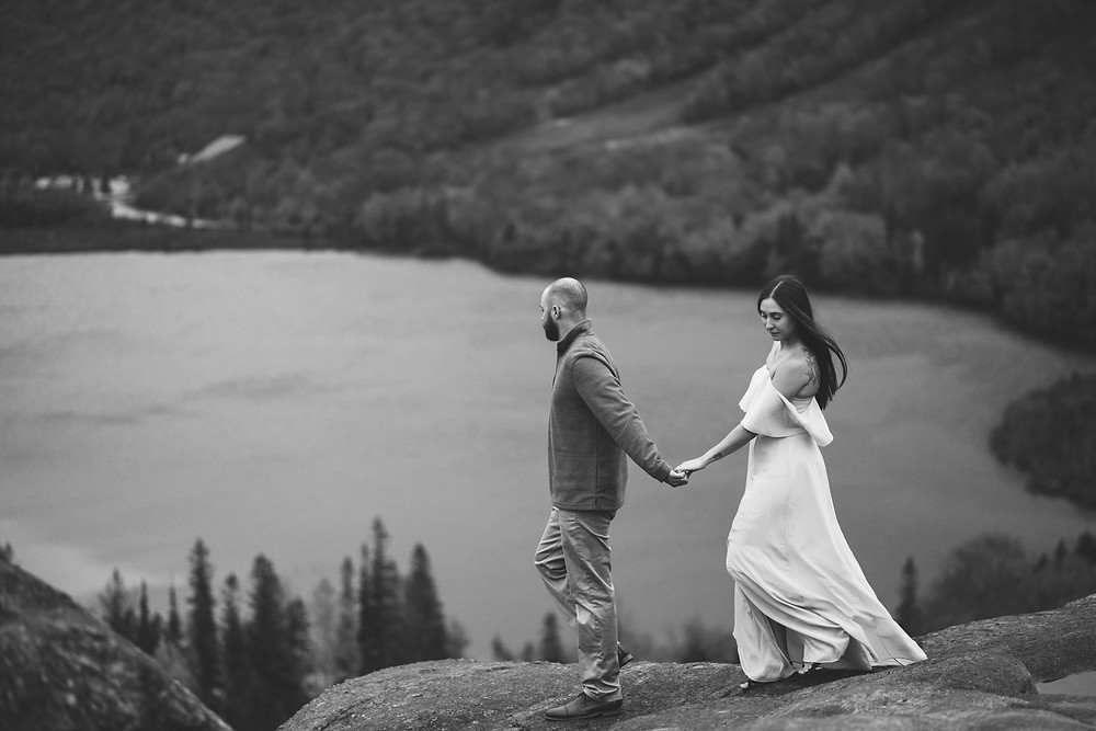 guy leading girl along mountainside in the white mountains during adventure elopement