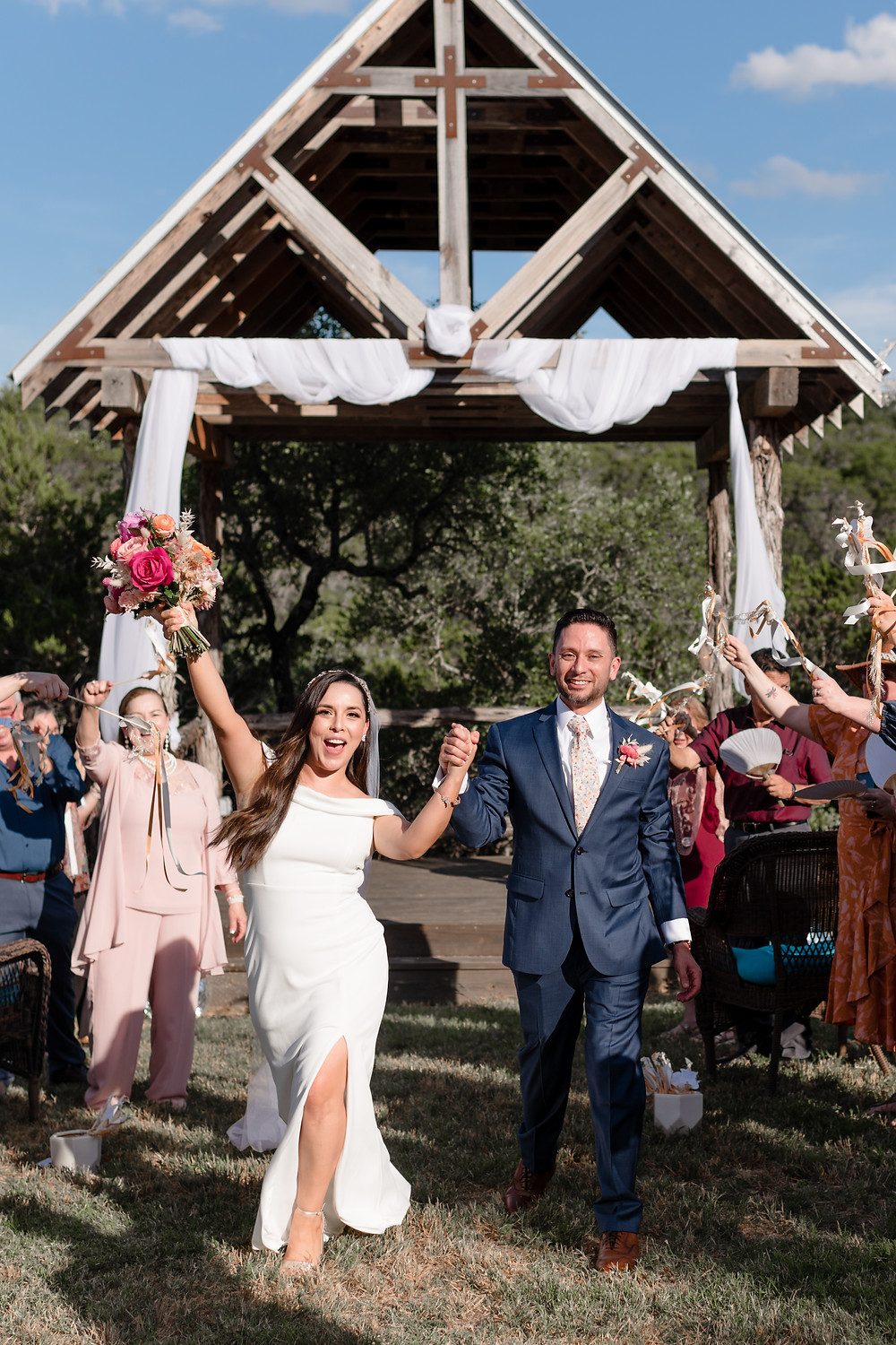 "the bride and groom celebrate walking back down the aisle after pronounced husband and wife. they are holding hands and the bride has bouquet raised high in the air. you can tell she is saying ""wooo!"". guests are in the background, on either side of them, waving ribbons"