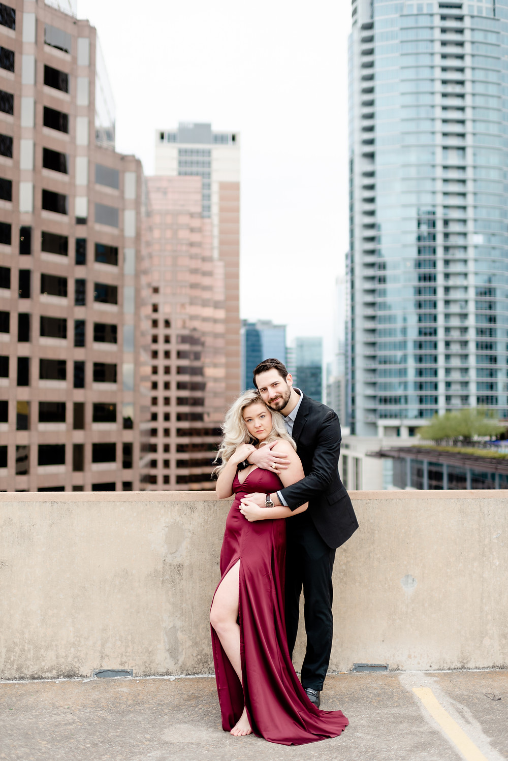 a couple in formal attire on the roof of a parking garage in downtown austin texas for their engagement photos