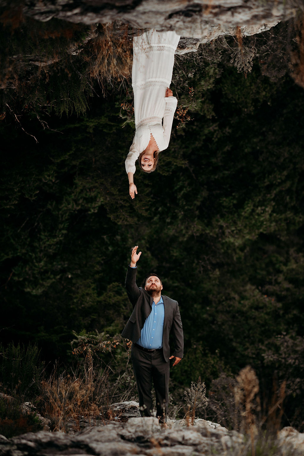 a composition image created in photoshop. the bride and groom are each reaching straight up in the air. The bride's photo is flipped so it looks like she is standing on the top of the photo, reaching down to the groom.