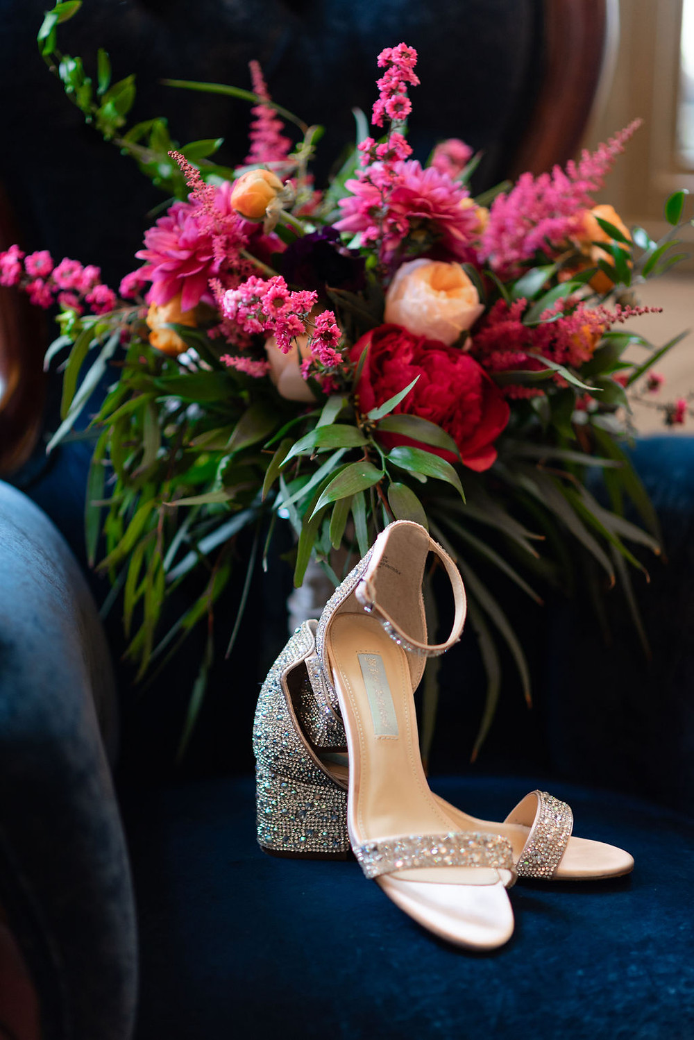 pink bridal bouquet on blue velvet chair with wedding shoes displayed. chat is in the foyer at villa antonia