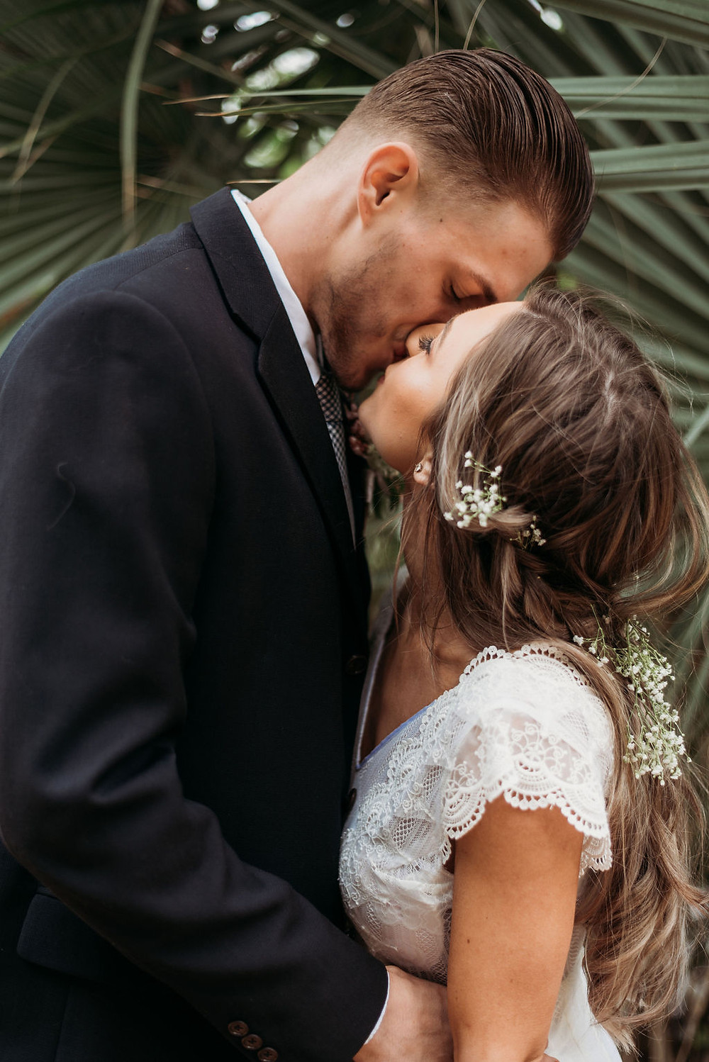 bride and groom kiss in front of palm trees next to lady bird lake during their austin elopement
