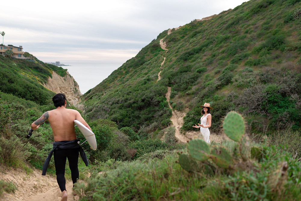 bride standing on hillside with a surfer running through the frame