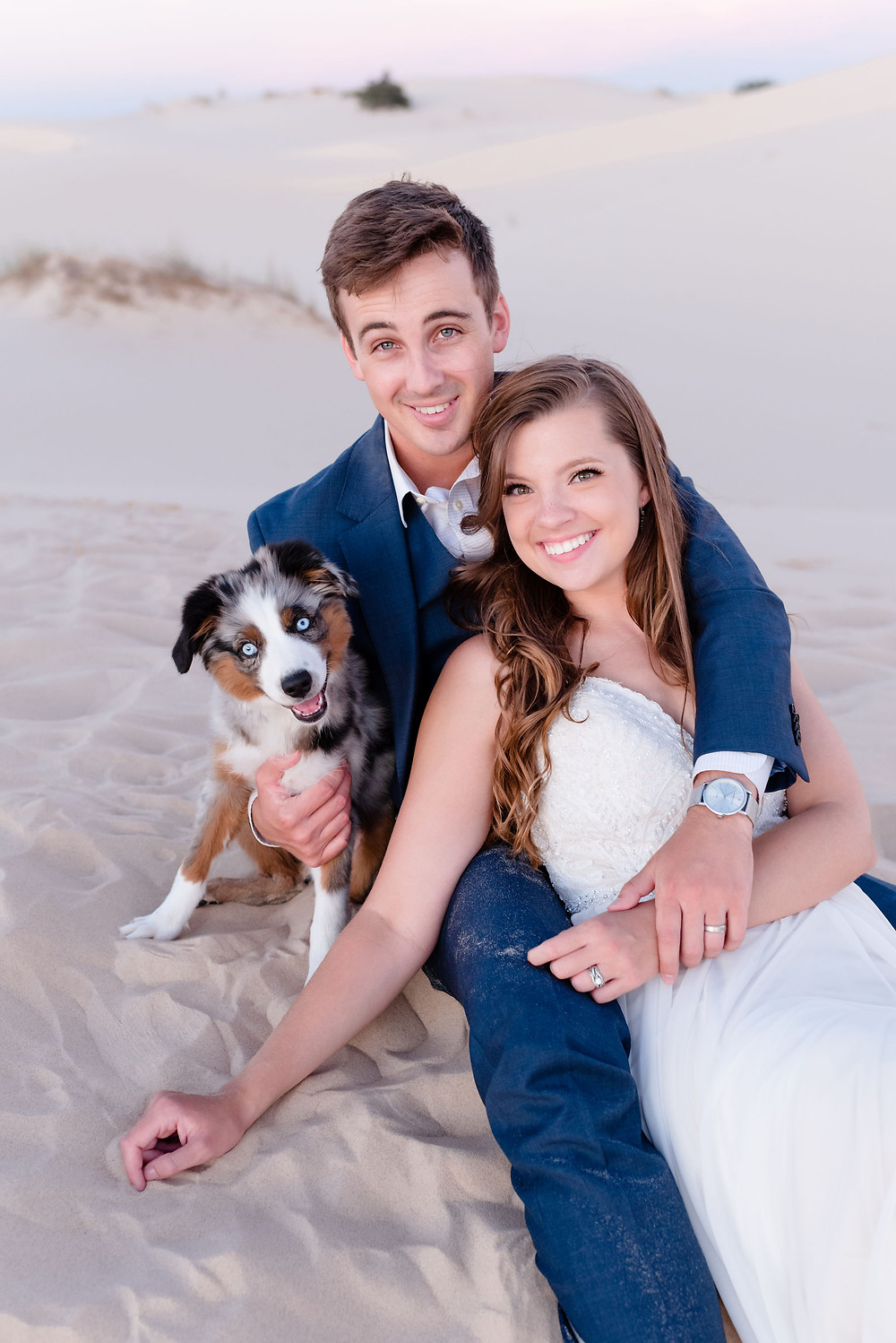 bride and groom sit in sand with puppy smiling at the camera
