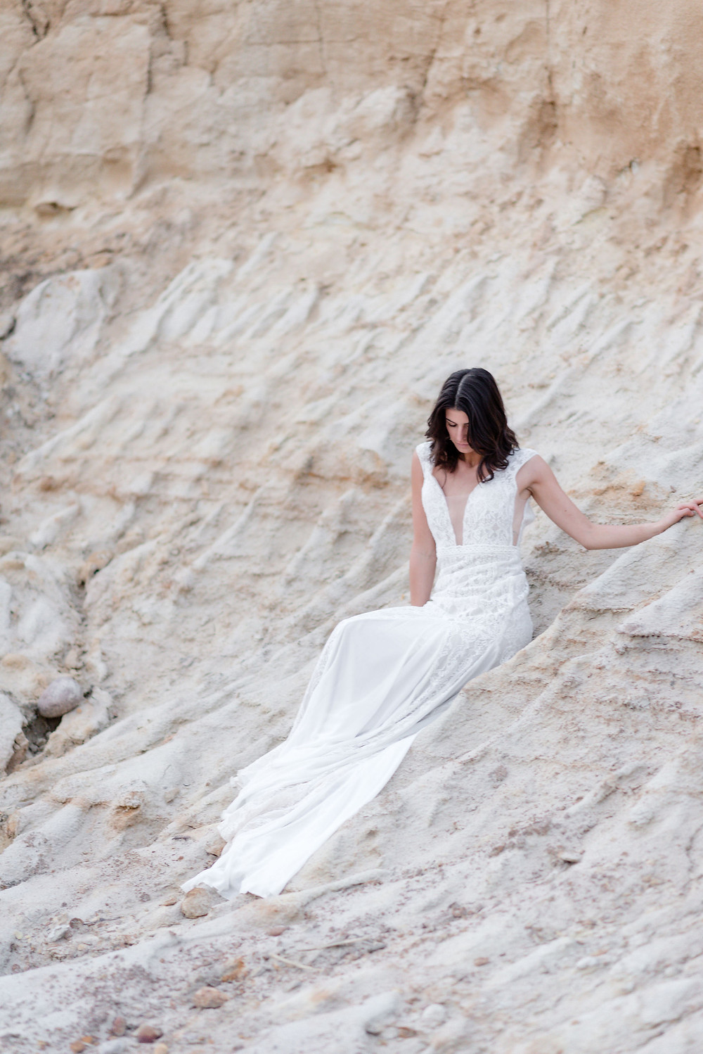 girl wearing wedding dress sitting in sand dune