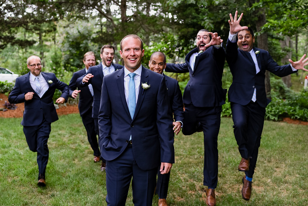 groomsmen running up behind groom to tackle him