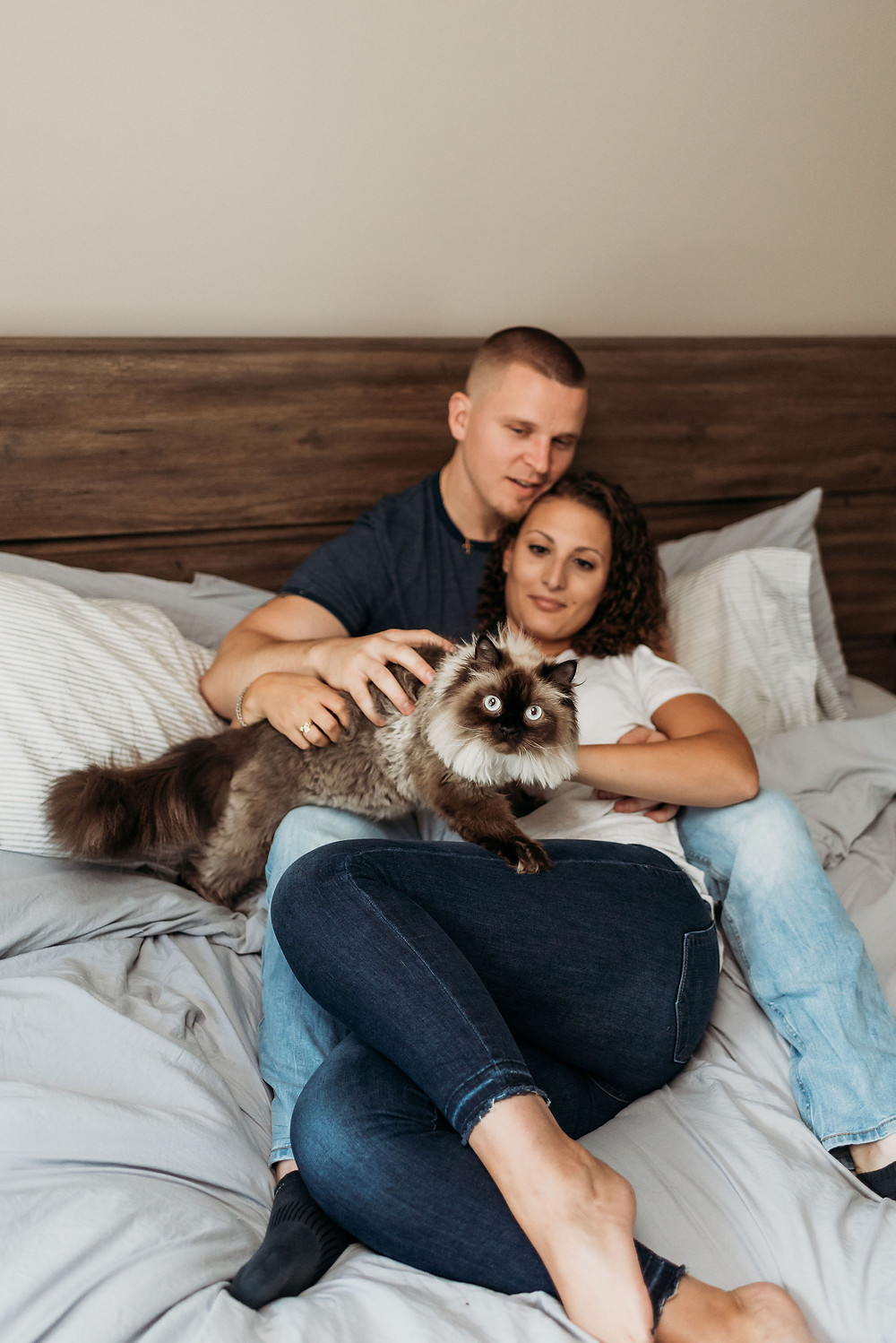 in home engagement session with couple posed laying on bed with cat
