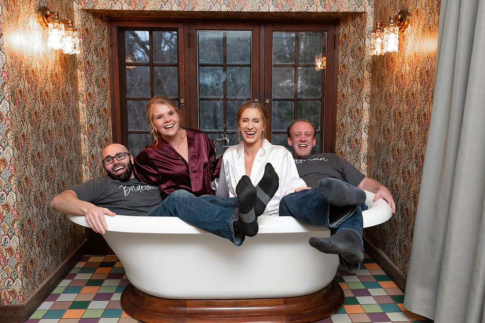 wedding party in the bathtub in the bridal suite of willowdale estate