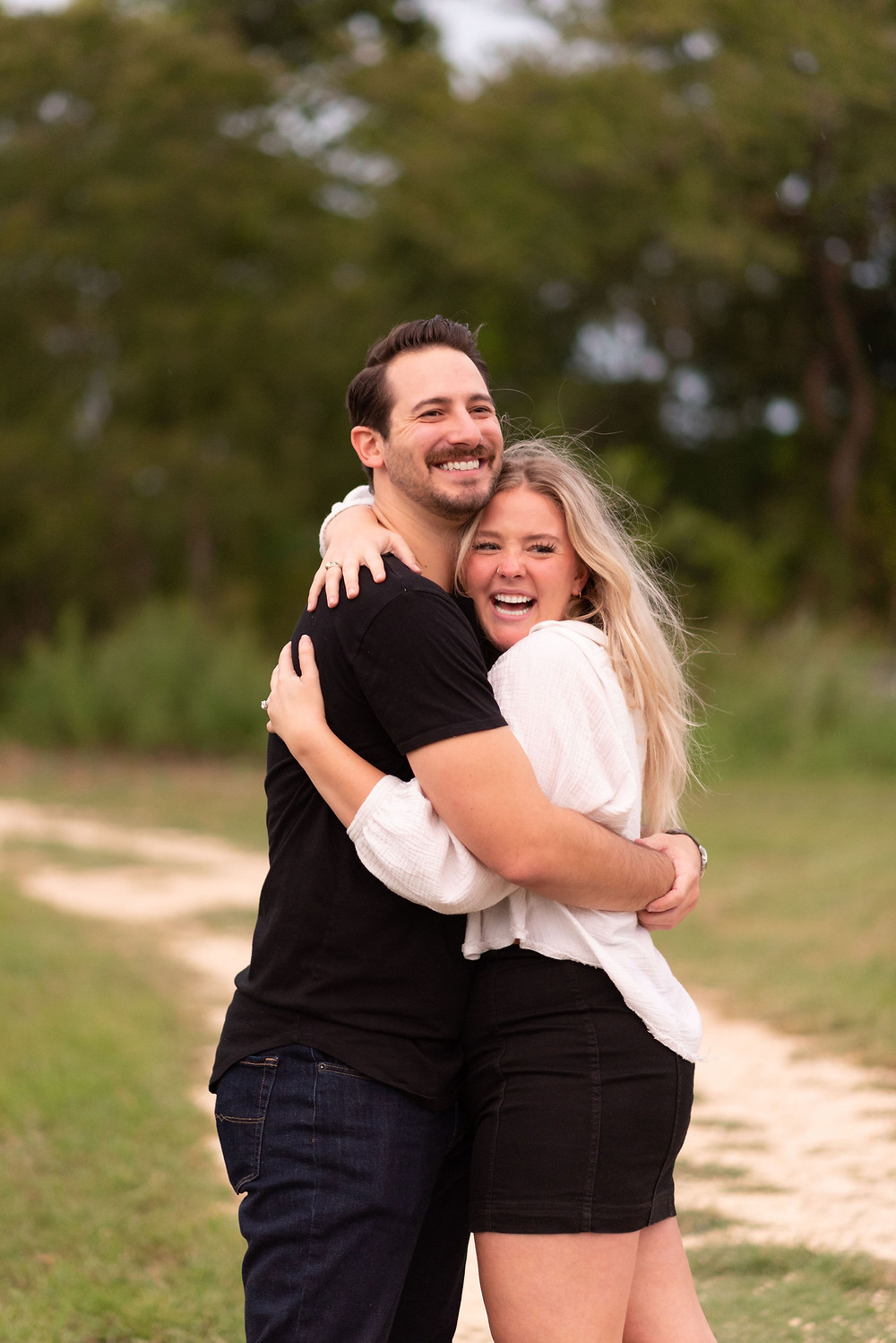 couple hugging and laughing after getting engaged